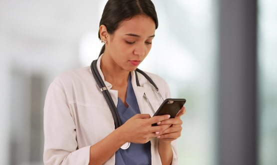 A female doctor texting on a smartphone