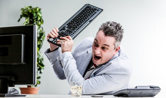 An angry man striking a computer with a keyboard