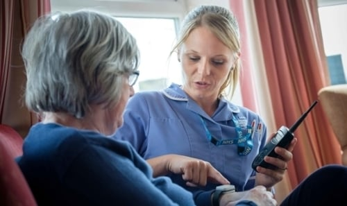 A care home nurse in Calderdale teaches a resident how their technology works