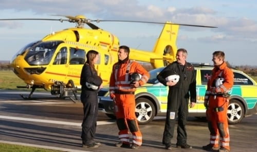 Paramedics with East Anglian Air Ambulance (EAAA) pose next to a helicopter